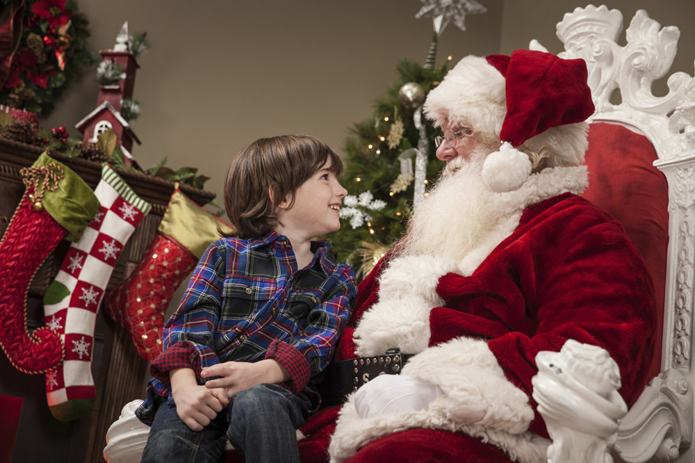 Excited Young Boy Sits on Santa's Lap