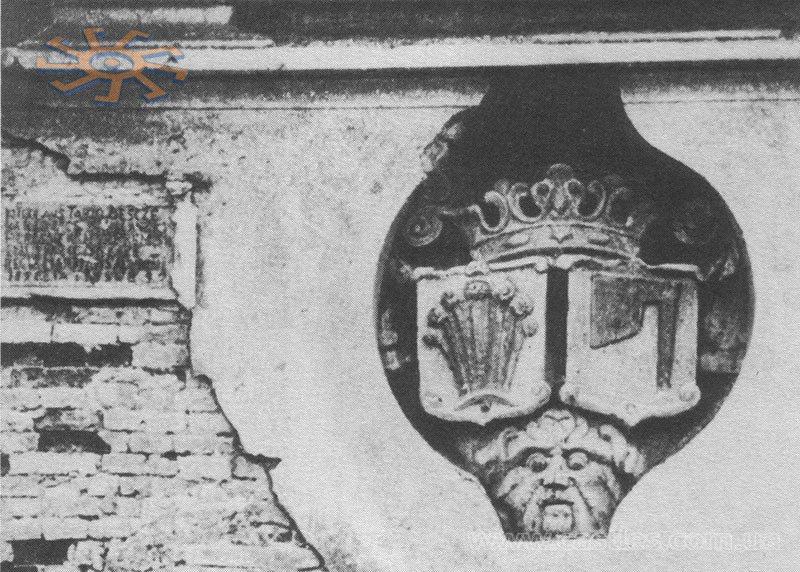 """Герб роду Тарло """"Топор"""" на стіні замку в Мурованому разом з написом, що згадує про відбудову замку в 1559 році. Фото 1905 року"""