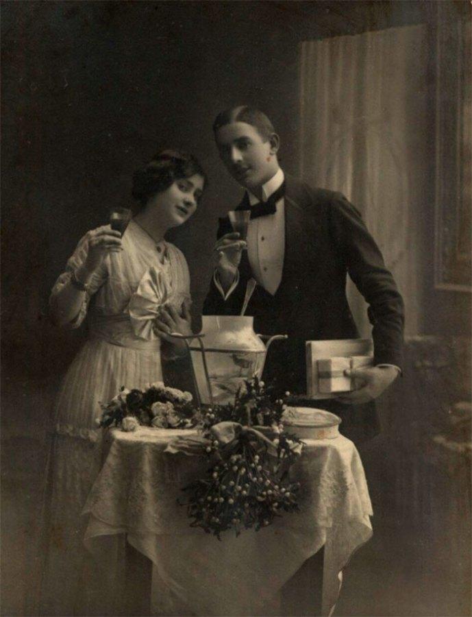 Пара з келихами в руках, біля накритого столу, оздобленого омелою, чоловік з подарунками. Фото 1900-1920 років.