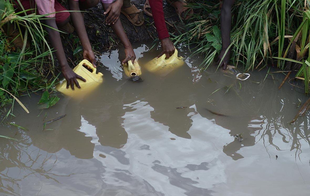 Діти набирають воду в болоті, Мвеа, Кенія