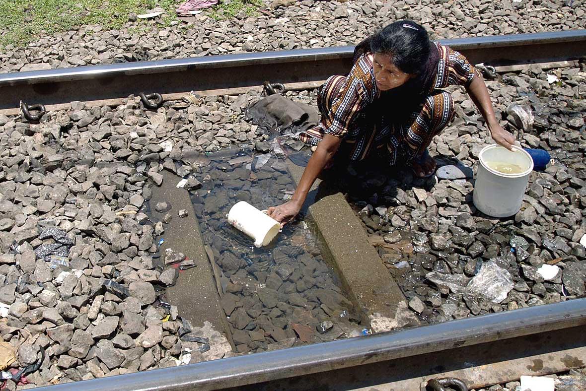 Мешканка з провінції набирає воду на залізничних рейках, Мумбаї, Індія.