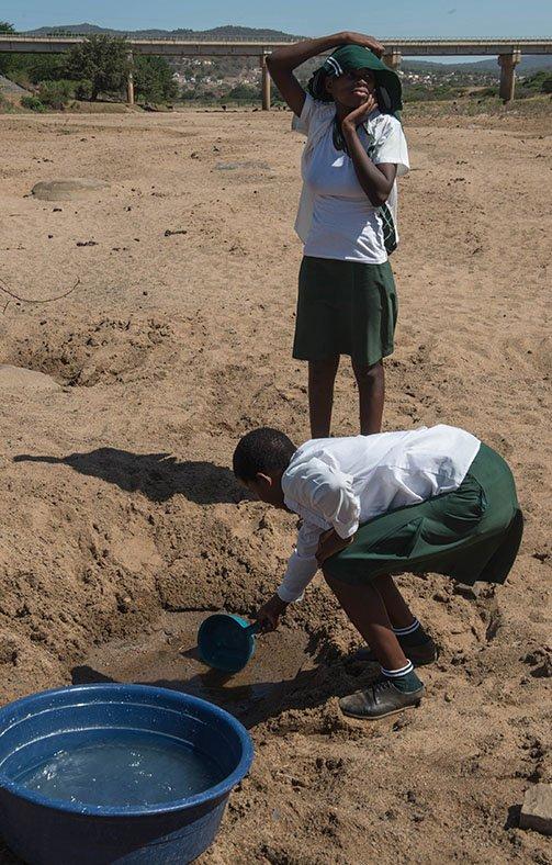 Школярка намагається отримати воду із пересохлої калюжі після засухи у Нонгомі, Південна Африка