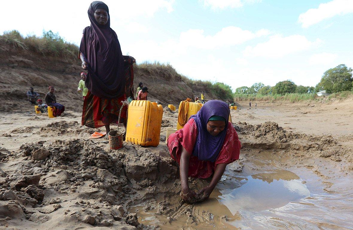 Люди збирають воду в пересохлому руслі річки, Шабелле, Сомалі.