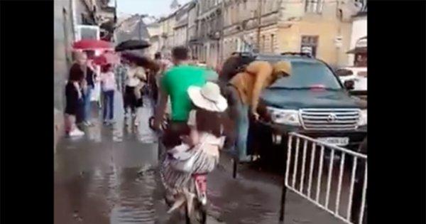 Львів'янин велосипедом перевозить людей через калюжу